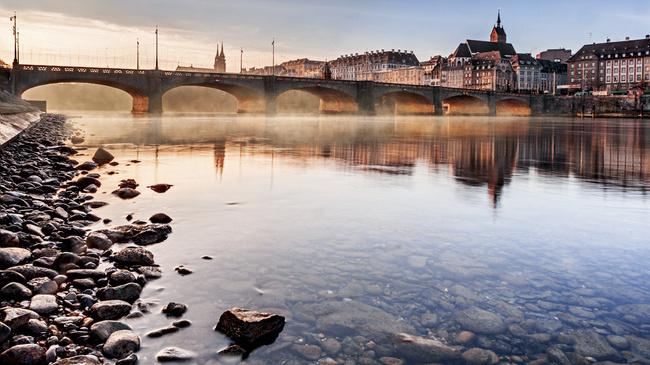 Schweiz. ganz natuerlich. Morgennebel ueber dem Rhein mit Mittlerer Bruecke.